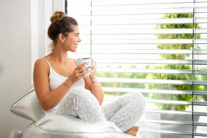 junge Frau trinkt Tee am Fenster